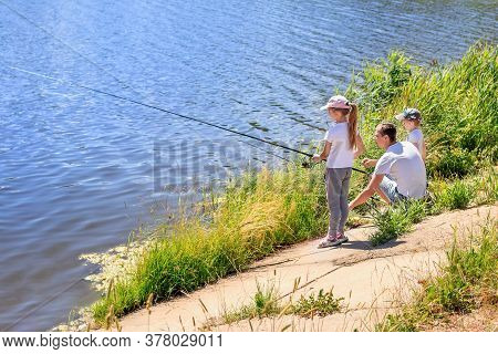 Daughter With Father And Brother Sit On The Shore Of The Lake With Rods And Catch Fish. Concept Of O