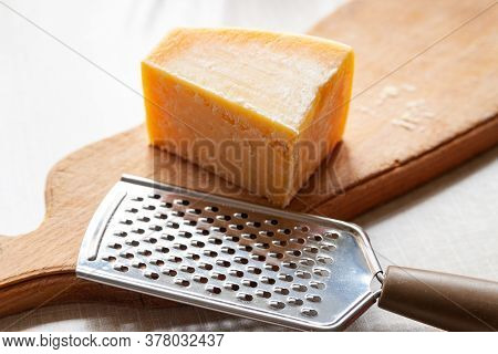 Parmesan Cheese. A Piece Of Cheese And Grater On A Wooden Board. Fine Grater For Grating Cheese. Tra