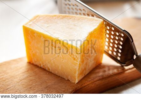 Cheese And Grater. Piece Of Parmesan On A Wooden Board. Grater For Grating Cheese. Traditional Food.