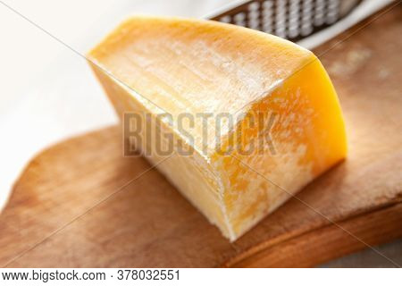 Piece Of Cheese. Piece Of Parmesan On A Wooden Board. Cheese Grater. Traditional Food.