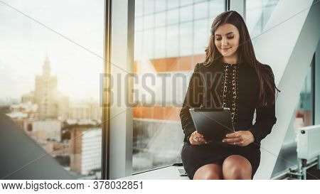 A Dainty Hispanic Businesswoman Is Sitting On A Modern White Bench Of A Business High-rise Coworking