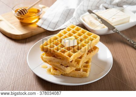 Plate With Delicious Waffles With Honey And A Slice Of Butter. Close-up