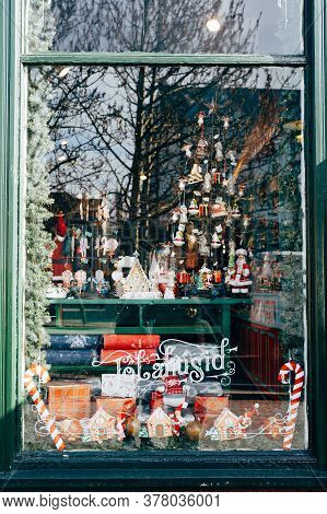 Christmas Window Decoration With Figurines And Toys With Street Reflection In Glass.