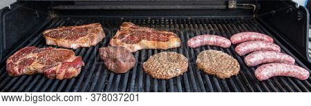 Raw Meat On The Grill That Has Been Seasoned With Steak, Hamburgers And Bratwurst.