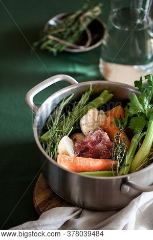 Ingredients For Cooking Bone Broth. Stock Pot With Veggies, Herbs, And Beef. Vertical Orientation