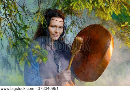 Middle Aged Woman Dressed In Shaman Costume Playing On Shaman Frame Drum In The Nature