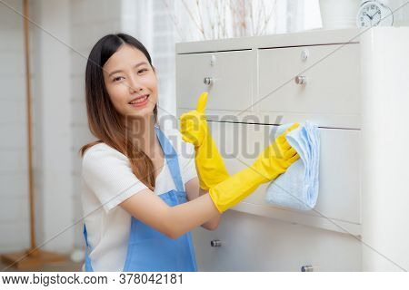 Young Asian Woman In Gloves Cleaning Home In Room, Housekeeper Is Wipe With Fabric, Housemaid And Se