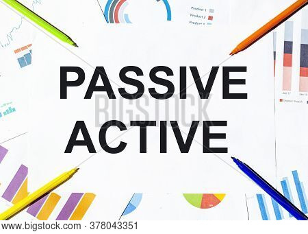 White Piece Of Paper With Text Passive Active On The Background Of The Graphs, Multi-colored Felt-ti