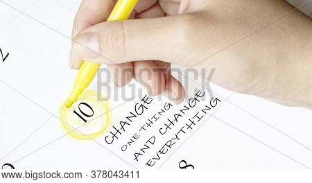 Hand Encircles A Date On A Calendar With Text Change One Thing And Change Everything Yellow Felt-tip