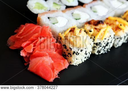 Seafood. Traditional Sushi And Rolls On The Dish. Black Background.
