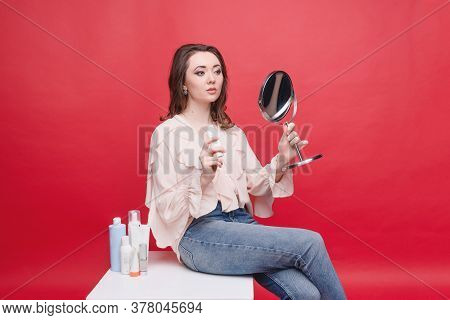 Attractive Young Girl Looks In The Mirror, Close-up. The Concept Of Youth, Beauty And Personal Care