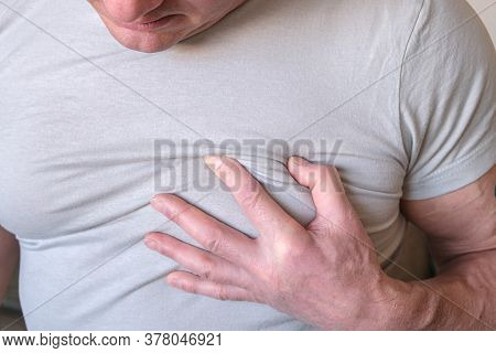The Man Clutched At His Chest. Heart Attack Angina On A White Background. Sick Person. Medical Exami