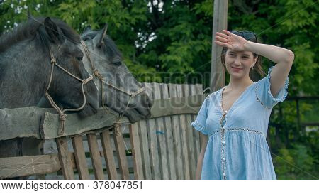 Young Smiling Woman Standing Near The Paddock With Horse Outdoors