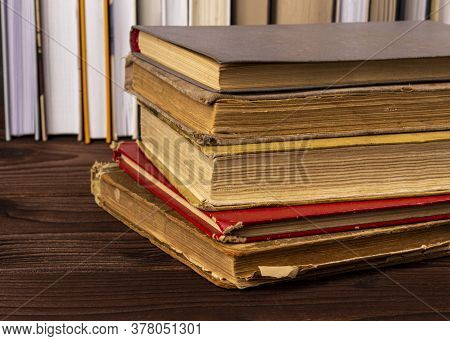 High Angle Close Up Of Stack Of Antiquarian Books Pile On Wooden Surface Against The Background Of N