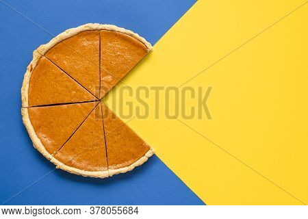 Above View With A Sliced Pumpkin Pie On A Bicolored Background. Home-baked Pumpkin Cake. Thanksgivin