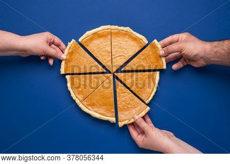 Top View With A Home-baked Pumpkin Pie Isolated On A Blue Colored Background. Three People Grabbing