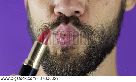 A Young Guy With A Beard Paints His Lips With Red Lipstick. Close-up Of A Bearded Man, He Painted Li