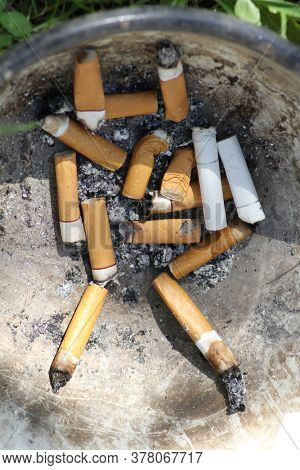 Old dirty cigarette butts in an iron bowl