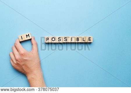 The Concept Of The Possible From The Impossible. Hand On A Blue Background With Wooden Blocks