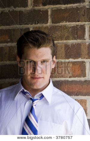 Man On Brick Wall Looking At Camera