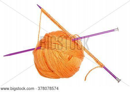 Purple Knitting Needles With Beginning Row Of Work Pushed Through Skein Of Bright Orange Yarn Formin