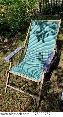 Retro Deck Chair With Striped Fabric Hammock And Shadows Of Tree Branches With Leaves. Outdoor Furni