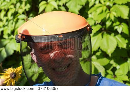 Toothy Smiling Man Wearing Protective Helmet For Grass Trimming, Outdoor Portrait
