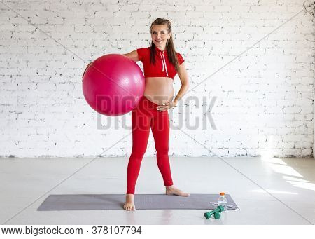 Young Pregnant Woman Standing With A Fitness Ball. Full Length Portrait