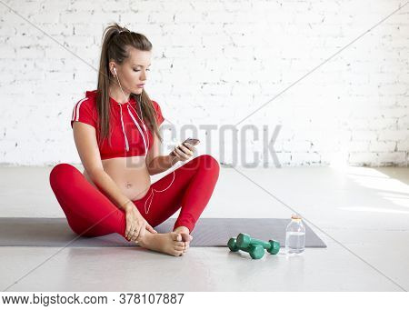 A Young Pregnant Woman Sits On A Floor And Listens To Music Through Headphones And A Mobile Phone. C
