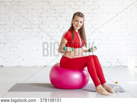 Smiling Young Pregnant Woman Working Out On A Fitness Ball With Dumbbells. Full-length Portrait
