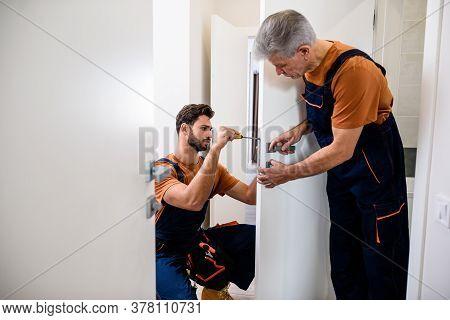 Two Locksmith, Repairmen, Workers In Uniform Installing, Working With House Door Lock Using Screwdri