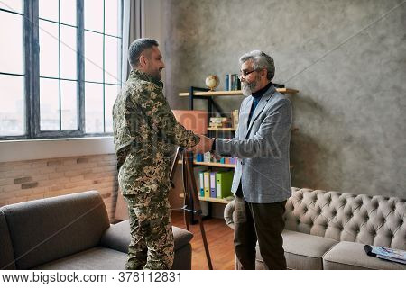Middle Aged Military Man Looking Happy, Shaking Hands With Psychologist After Therapy Session. Soldi