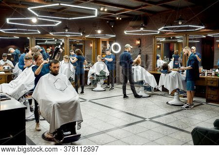 Modern Barbershop. Professional Barbers Serving Clients In The Modern Loft Style Barber Shop. Genera