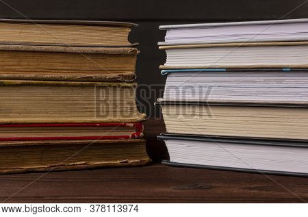 A Stack Of Old Books Is On The Table Next To A Stack Of New Books. Books In The Library On The Table