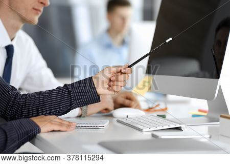Business Woman And Man Are Discussing Questions While Using Computer And Blocknote In Modern Office,