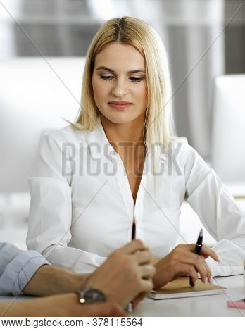 Group Of Business People Discussing Questions At Meeting. Headshot Of Blonde Businesswoman While Smi