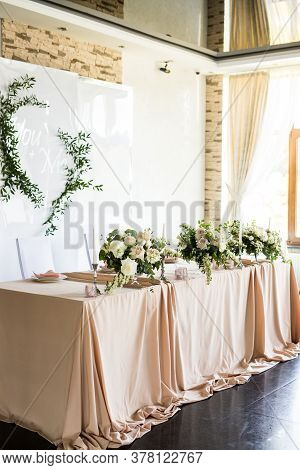 Side View Of The Presidium Of The Newlyweds At The Wedding. Table For The Bride And Groom With Flowe
