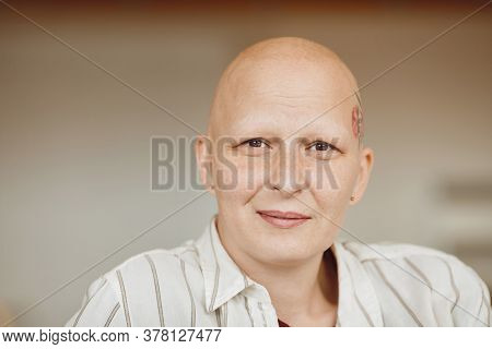 Minimal Head And Shoulders Portrait Of Bald Adult Woman Looking At Camera And Smiling While Sitting