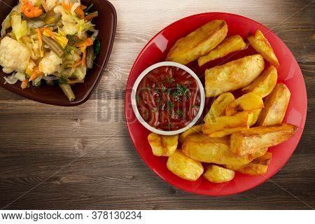 French Fries With Ketchup On Brown Wooden Background. French Fries On Red Plate With Vegetable Salad