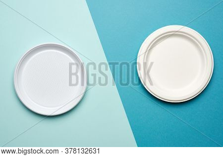 Empty White Plastic Plates And White Paper Disposable Plates On A Blue Background, Top View. The Con