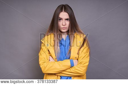 An Angry Young Girl, Dressed In A Blue Sweater And A Yellow Raincoat, Clasped Her Hands On Her Chest