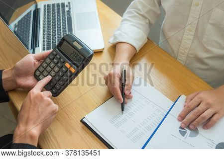 Bank Employees Sit And Work And Check The Financial Summary. Working In An Office, A Consultancy And