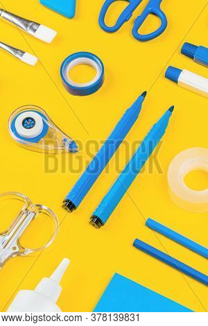 Assorted Office And School White And Blue Stationery On Bright Yellow Background. Organized Knolling