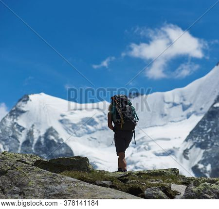 Zinal, Switzerland - July 19, 2019: Back View Of Traveler With Backpack Hiking Alone In Mountainous