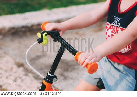 Blurred Child Sits On A Bicycle. Father's Day. Child's Hands On The Hand Of An Orange Bike For Child