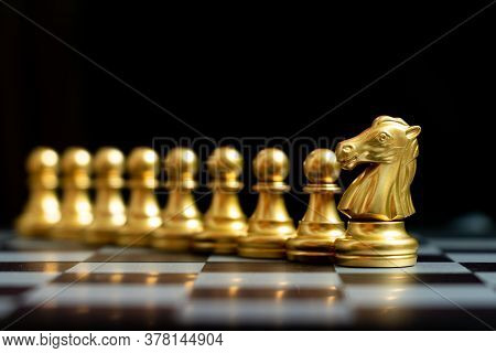 Gold Knight Chess Piece Stand With Pawn On Black Background (concept Of Teamwork, Management)