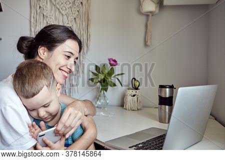 A Woman With A Child Works At A Computer. Concept Of Work From Home And Home Family Education. Mom A