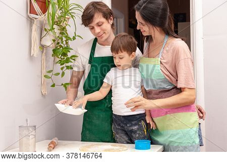 Mother, Father And Son Are Preparing Dough For The Cookies In The Kitchen. Little Boy Helps Mother A