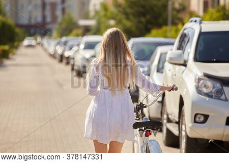 Young Blond Woman In White Dress Walks Away With Bike Near Cars At City, Rear View