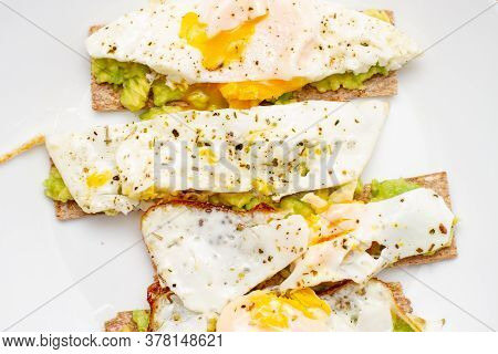 Bruschetta With Avocado And Poached Egg. Healthy Breakfast On A White Plate On The Kitchen Table. Ve